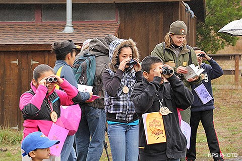 A park ranger consults a bird book as children around her look through binoculars.
