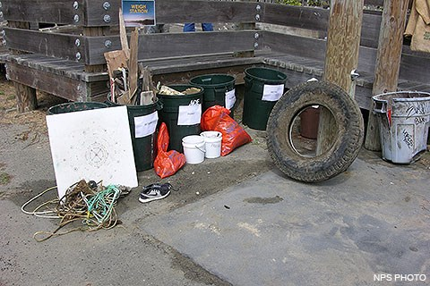 Garbage that was collected from Drakes Beach included (from left to right, some of which are in dark green garbage cans): ropes, a large white cutting board, wood, a pair of sneakers, foam, a three-foot diameter tire, and a light blue garbage can.