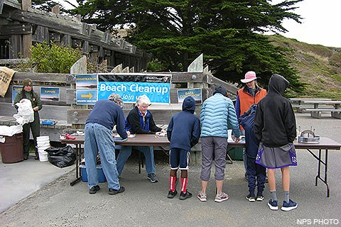 Five volunteers sign forms at a folding table while a ranger on the left prepares bags and buckets for the volunteers to use as they collect marine debris from the beach.