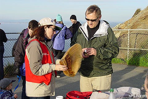 A female volunteer in a red vest showing gray whale baleen to a male visitor.