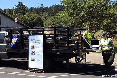 Two uniformed park employees loading electronic waste into a gray stake bed truck.