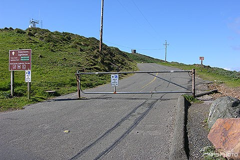 A metal gate blocking a road leading up a hill with a brown sign on the left.