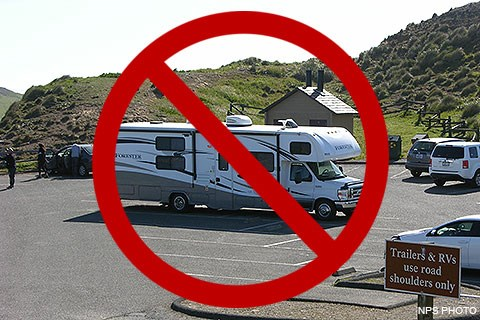 A large recreational vehicle parked in a small parking lot. A red circle with a diagonal line indicates that doing so is prohibited.