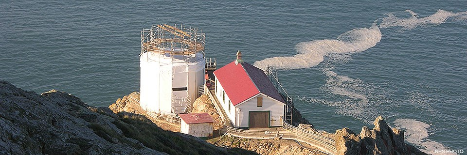 Three structures—a tower, a large rectangular building, and a small square structure—sit on a rocky headland above the Pacific Ocean. The roof and rafters of the lighthouse tower have been removed and scaffolding and white fabric surrounds the tower.
