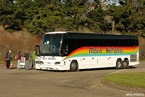 Five visitors boarding a coach-sized bus that is decorated with a rainbow-colored horizontal stripe.