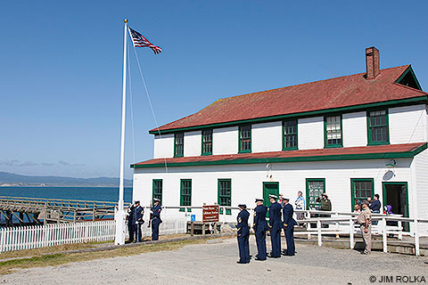 U.S. Coast Guard personnel and park visitors standing at attention and saluting as the U.S. flag is raised up a flagpole at the Historic Lifeboat Station at Chimney Rock.