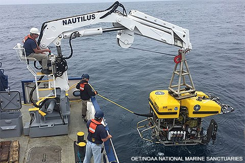 Three men on a ship hoisting a yellow remotely operated vehicle from the ocean.