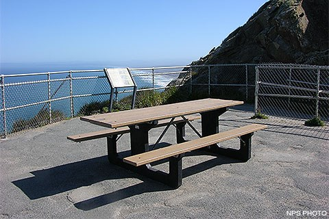 A picnic table in the middle of a paved observation deck, surrounded by chain-link fencing with a view looking out across the ocean and the shoreline.