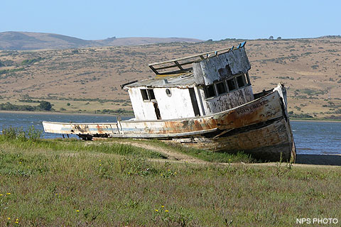 A derelict fishing boat on the edge of Tomales Bay with Bolinas Ridge in the background.