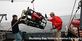 Two individuals launching a robotic submersible. Photo courtesy Monterey Bay National Marine Sanctuary
