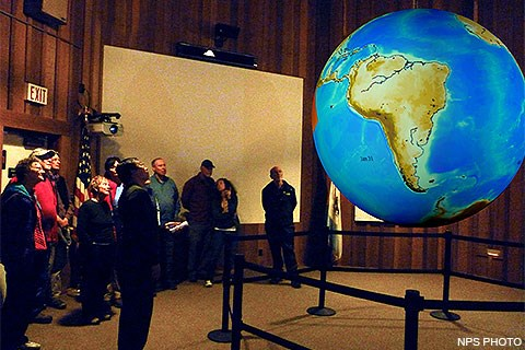 A park ranger and nine visitors looking at an image of Earth projected on a sphere which is hanging in the middle of an auditorium.