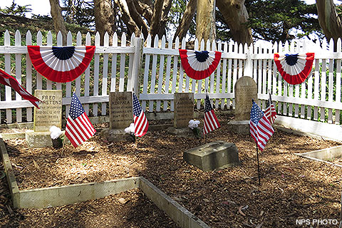 Five graves with off-white headstones surrounded by a white picket fence on which red-white-and-blue bunting is hung.