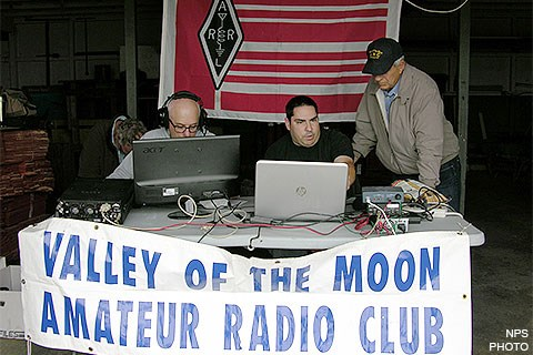 Three men sitting at a folding table on which there are laptops and radio equipment. A white banner with blue letters identify them as members of the Valley of the Moon Amateur Radio Club is hanging from the front of the table.
