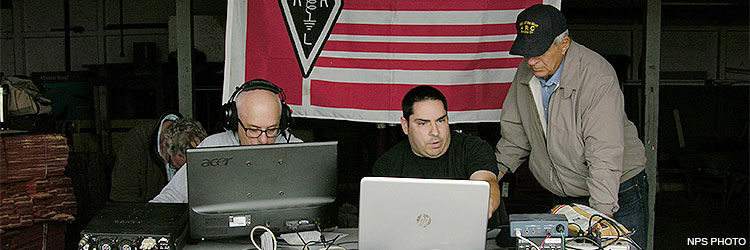 Three men sitting at a folding table on which there are laptops and radio equipment. A red, white, and black flag hangs in the background.