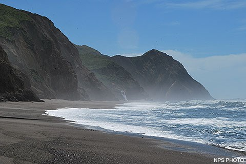 Pacific Ocean waves wash ashore onto a sandy beach from the right. Bluffs rise from the beach on the left. A tall headland rises in the center.