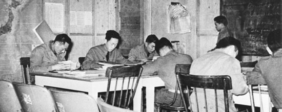 historic photo of Japanese-American soldiers studying at tables