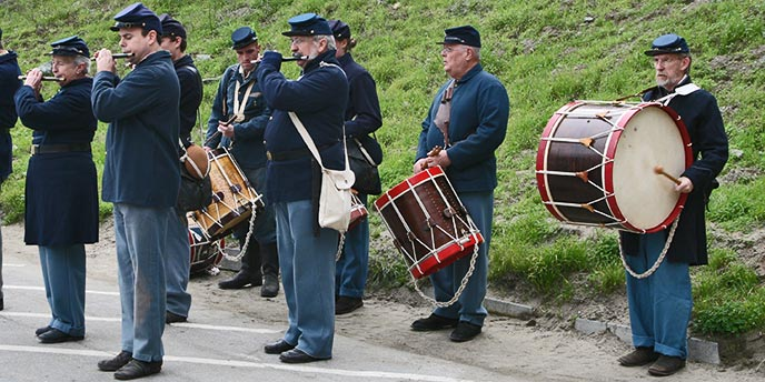 Nine male Civil War reenactors in blue uniforms standing on the edge of a parking lot facing left playing drums and piccolos with a green hill behind them sloping upwards.