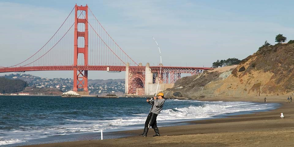 fisherman reels in his line on baker beach with bridge in the background