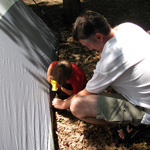 father and son set up tent