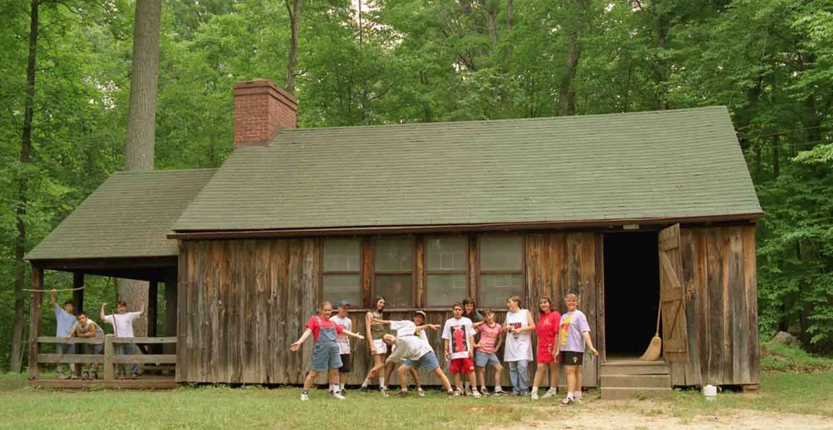 children stand in front of cabin