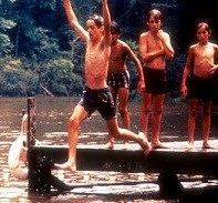 Young camper jumping off a dock into the lake