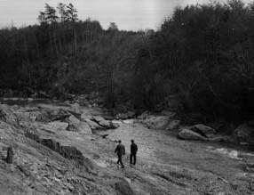 Two men walking along Quantico Creek in the early 1900s