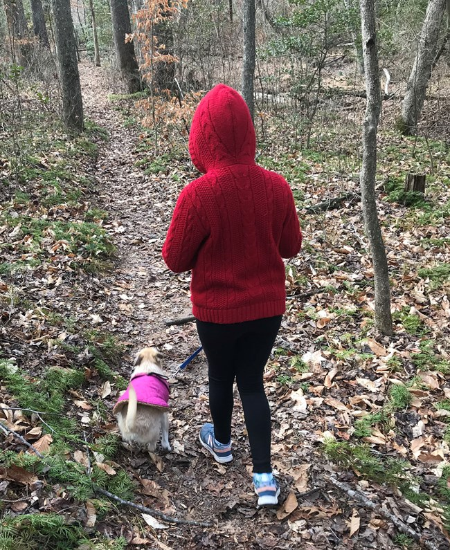 A girl in a red hooded jacket and her dog walk the trail to the letterbox