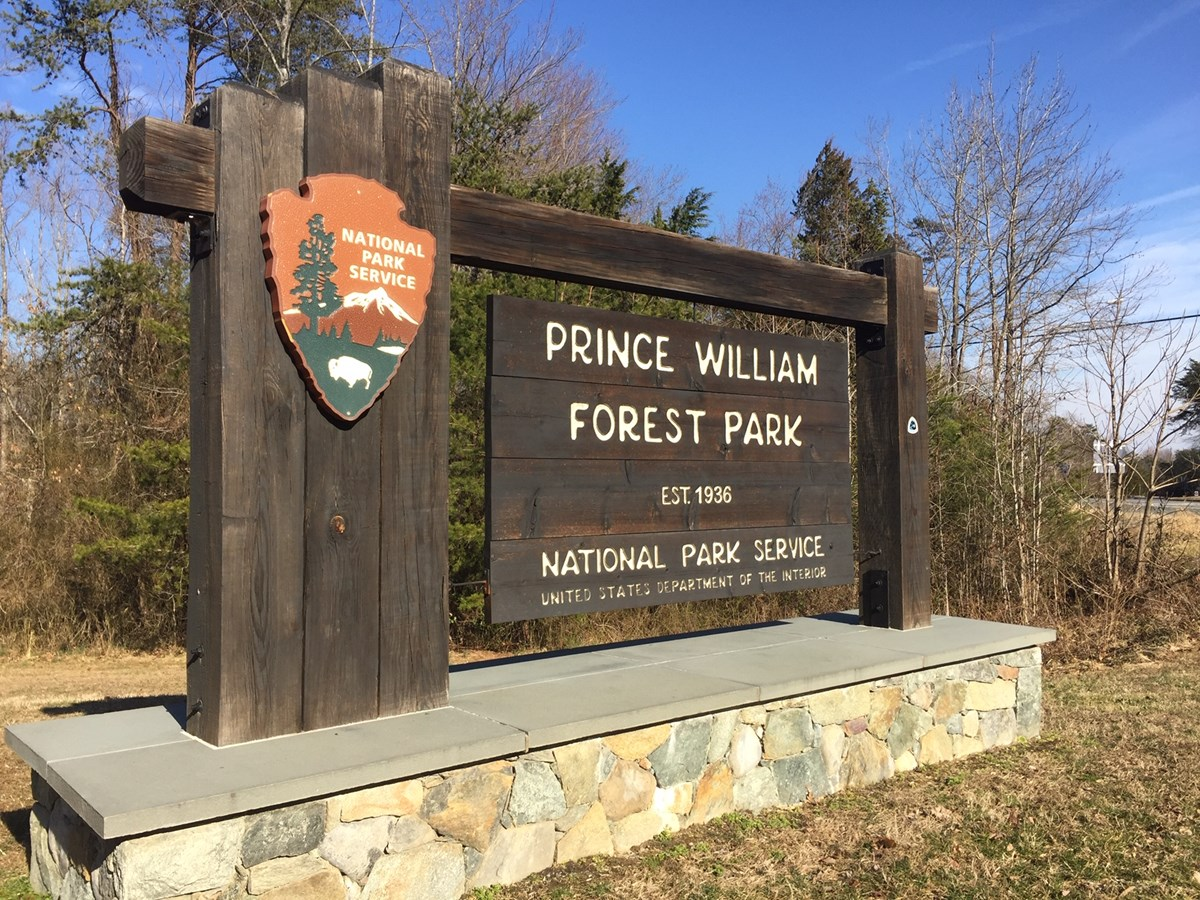 a large wooden sign on stone footings. sign states Prince William Forest Park