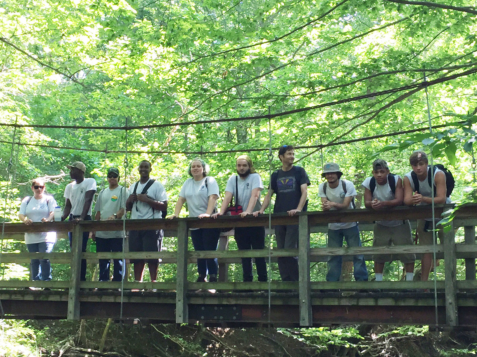 Nine YCC members and a leader stand on a bridge over the Quantico Creek.
