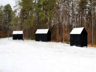 3 sleeping cabins covered in snow
