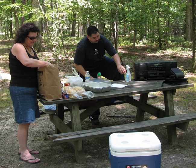 A woman and man unload camping supplies