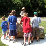 group of kids listening to a ranger program, given by a ranger, standing near a large piece of petrified wood