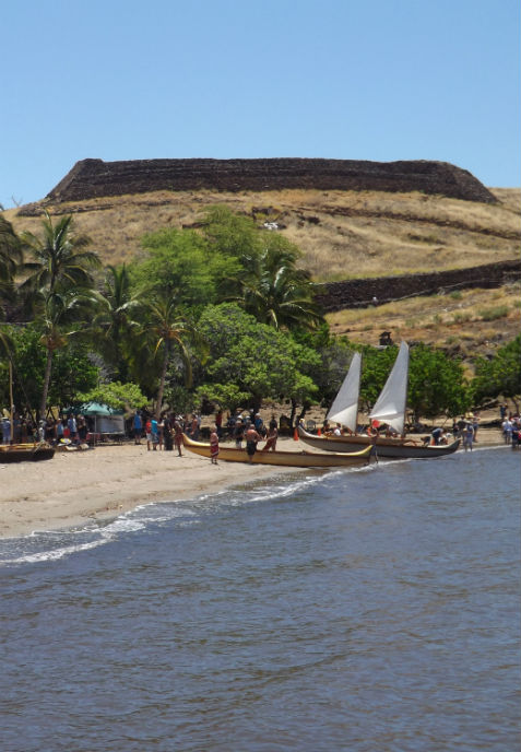 Visitors gather along Pelekane Beach during a Hawaiian Cultural Festival. Canoes along the shore with Pu'ukohola Heiau rising in the background.