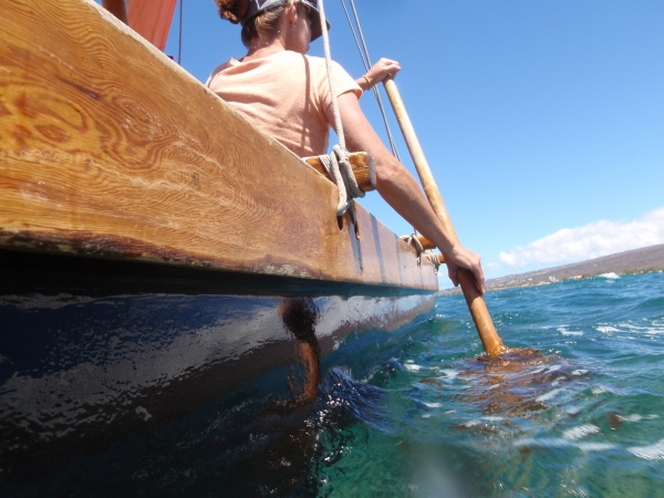 A woman paddles a double-hulled canoe