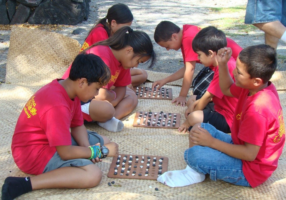 Students challenge each other in a Hawaiian checkers game.
