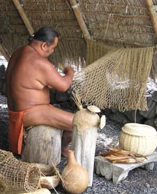 Cultural Demonstrator prepares  the net of a cape to which Ti leaves are woven.