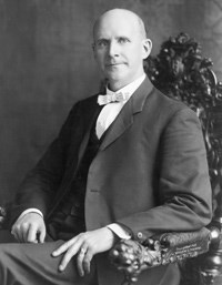 Eugene V. Debs seated in an ornate wooden chair.