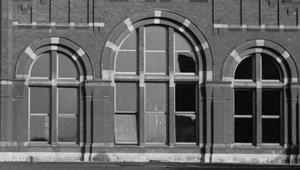 Three brick arches housing windows.