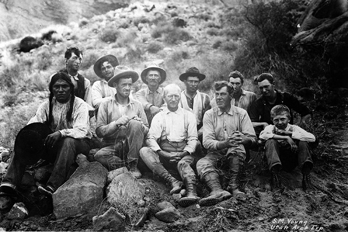 Historical photo of a group of men sitting on the ground in scrubby desert brush and rocks.