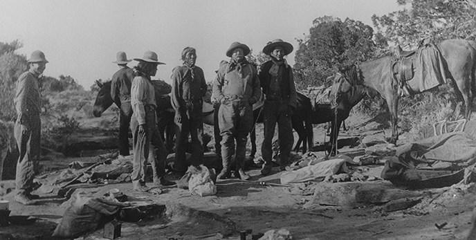 Historic photo of Teddy Roosevelt and party sanding around on slickrock.