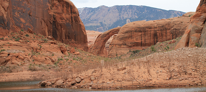Rainbow Bridge. Navajo Mountain in the background. Water in the foreground.