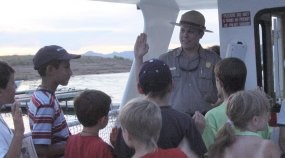 A Park ranger holds one hand in the air. He is surrounded by children. They are on a boat.