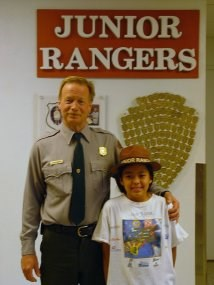 A Park Ranger stands with a child in a ranger hat in front of a sign that says Junior Rangers.