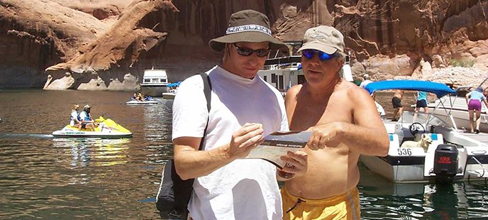 Two men read a brochure while standing on a dock. Various boats are behind them.