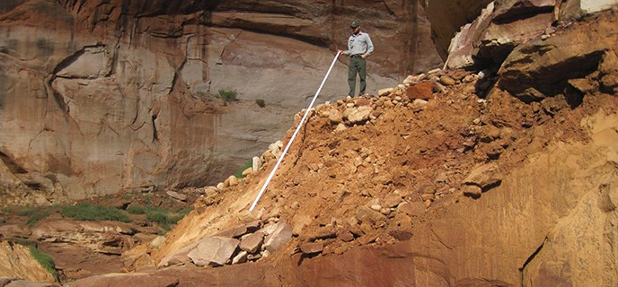 Park Ranger stands on top of a sandy landslide holding a measuring stick to the bottom.