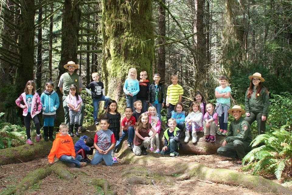 Three rangers and class take picture under Grandfather Spruce tree.