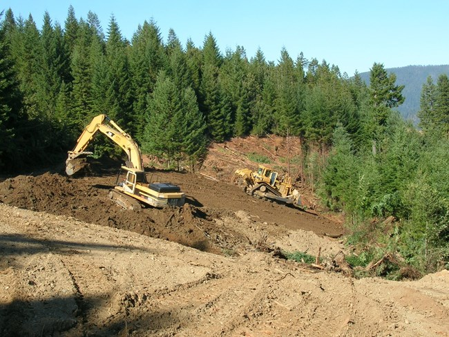 Heavy machinery removes old logging roads. Forests are in the background.