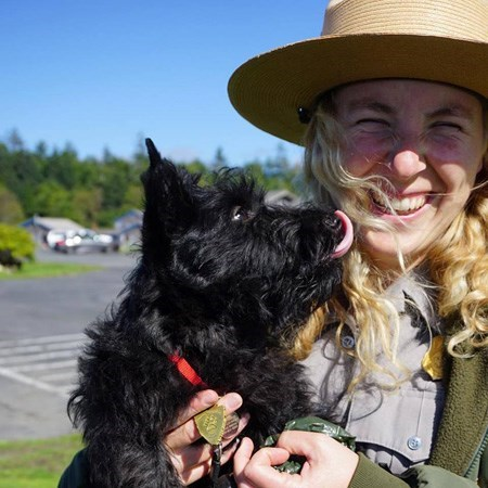 A black dog licks a park ranger.