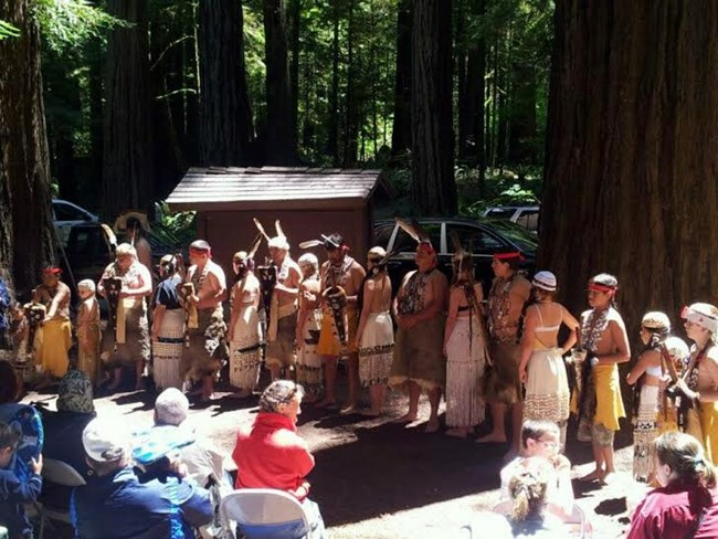 Tolowa dancers line up in front of a crowd.