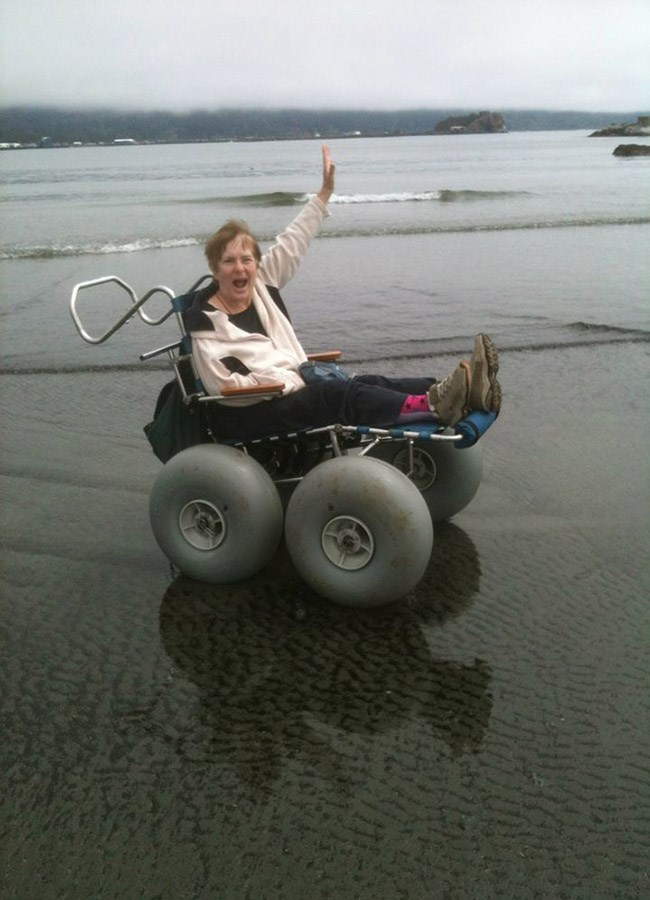 A woman in a beach wheelchair smiles and waves